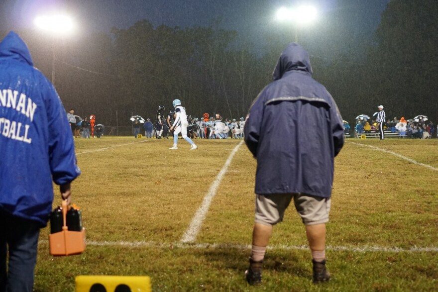 Standing in a drizzling rain, Hannan head football coach Kellie Thomas toes the sideline as she watches a punt return.