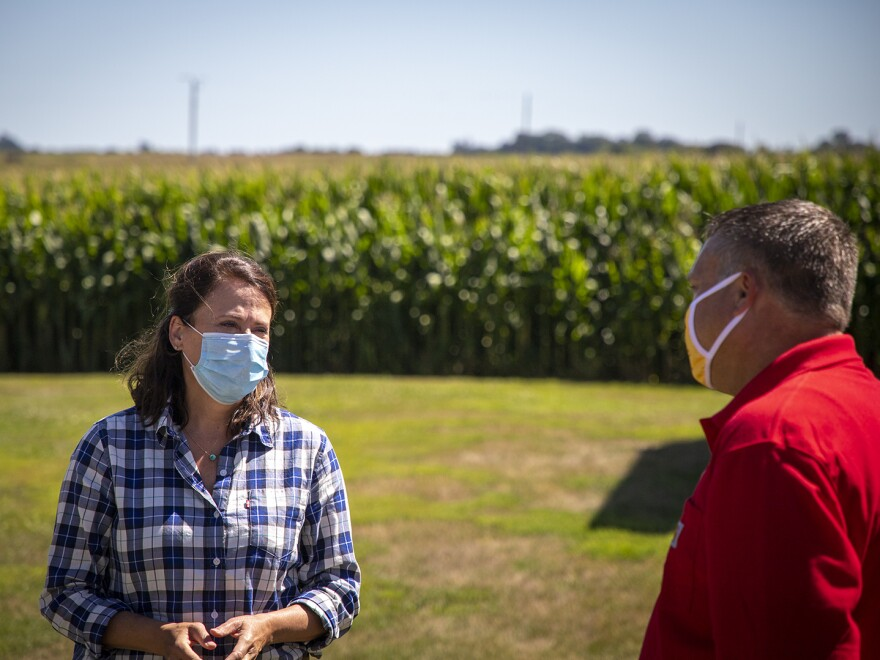 Democrat Theresa Greenfield, a real estate executive from Des Moines, talks with Trent Hatlen, who farms and raises hogs near Rembrandt, Iowa, on Aug. 11.