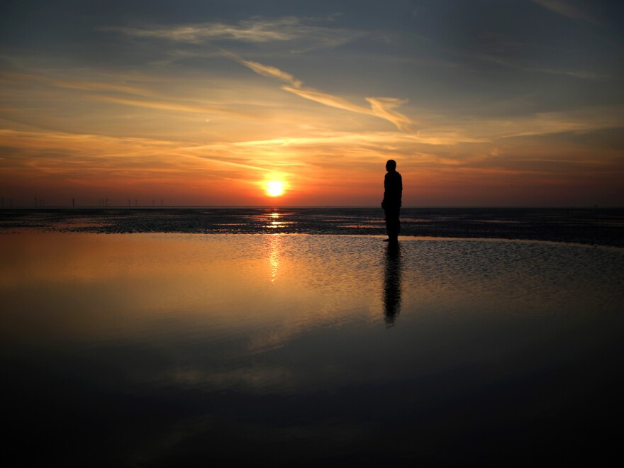 """One of the life-size body cast statues of """"Another Place"""" created by the artist Antony Gormley looks out over the Mersey Estuary at sunset at Crosby beach on April 15, 2014, in Crosby, United Kingdom."""
