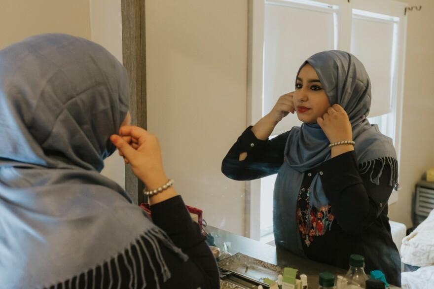 Ammal, 18, adjusting her hijab in the mirror.