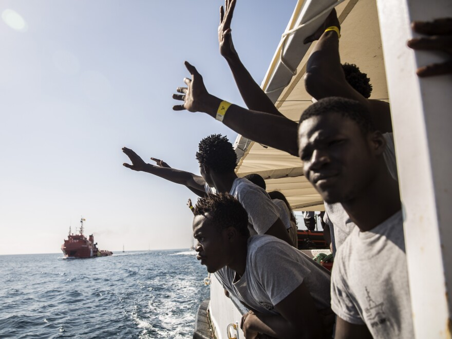 Migrants aboard the Open Arms aid boat, run by Spanish humanitarian group Proactiva Open Arms, react as the ship approaches the port of Barcelona, Spain, on July 4. The aid boat sailed to Spain with 60 migrants rescued in waters near Libya, after it was turned away by both Italy and Malta.
