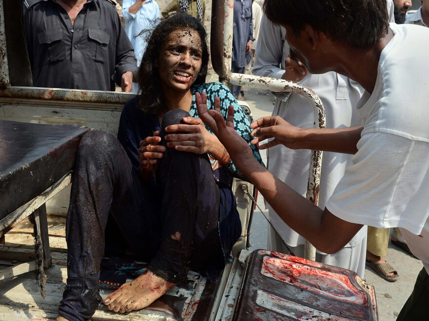 A man helps an injured woman on her arrival at the hospital after two suicide bomb attacks on All Saints Church in Peshawar on Sunday.