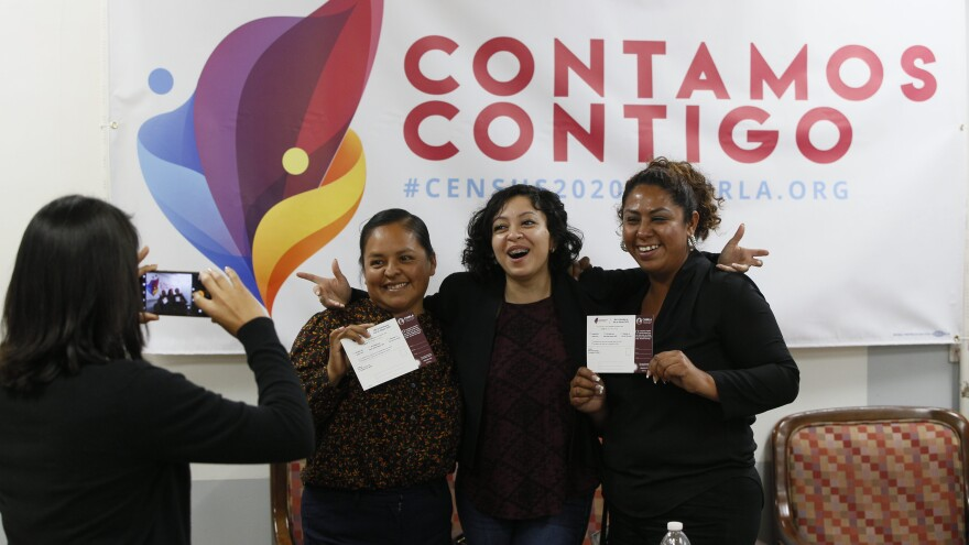 Diana Escamilla (center), an organizer with Coalition for Humane Immigrant Rights in Los Angeles, poses for a photo with volunteers Angeles Rosales and Janet Mendez in front of a 2020 census outreach campaign poster in Spanish.