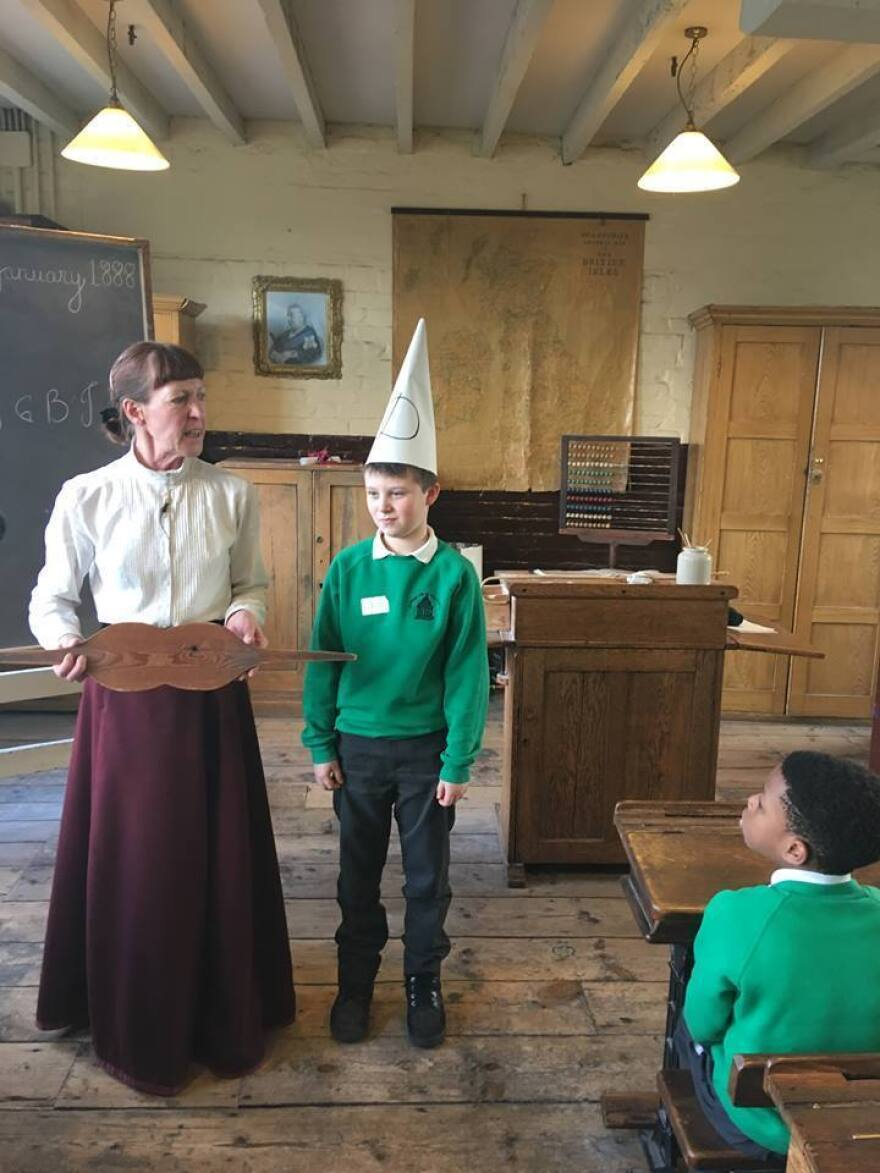 Miss Perkins chastises a visiting student with a dunce cap.