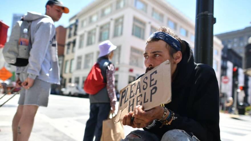 A man panhandles along a sidewalk in downtown San Francisco, California on Tuesday, June, 28, 2016.