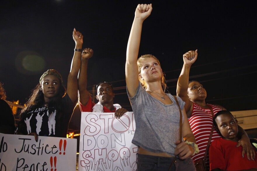 Mourners raise their fists during a night rally in honor of Alton Sterling outside the Triple S Food Mart in Baton Rouge, La., on July 11. Sterling was one of several men killed in police shootings this year.