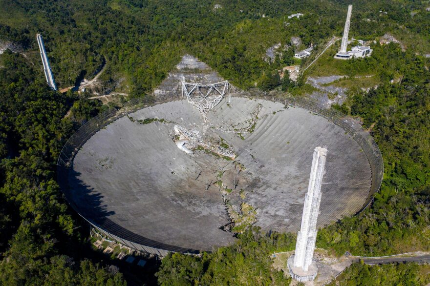This aerial view shows the damage at the Arecibo Observatory after one of the main cables holding the receiver broke in Arecibo, Puerto Rico, on Dec. 1, 2020. The radio telescope in Puerto Rico, which once starred in a James Bond film, collapsed Tuesday when its 900-ton receiver platform fell 450 feet (140 meters) and smashed onto the radio dish below. (Ricardo Arduengo/AFP via Getty Images)
