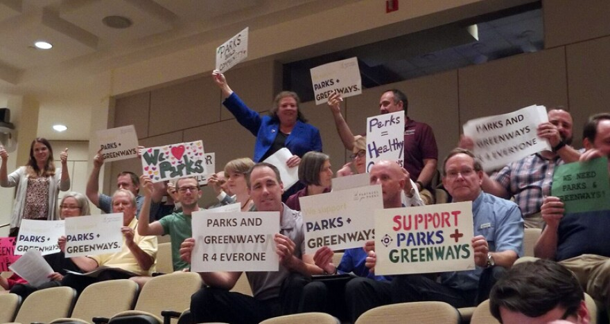 Supporters of more funding for parks and greenways waved signs at Wednesday's county commission meeting.