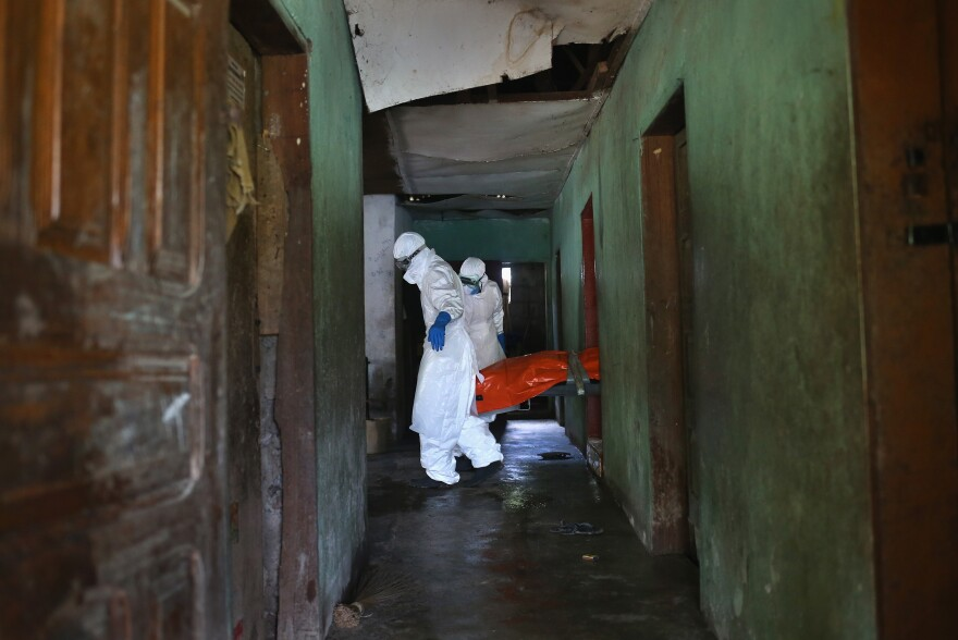 The protective gear worn by  Ebola burial teams is critical: A corpse can be contagious for up to 7 days. These workers are carrying the body of a woman who died of the virus in her home in a suburb of Monrovia, Liberia.