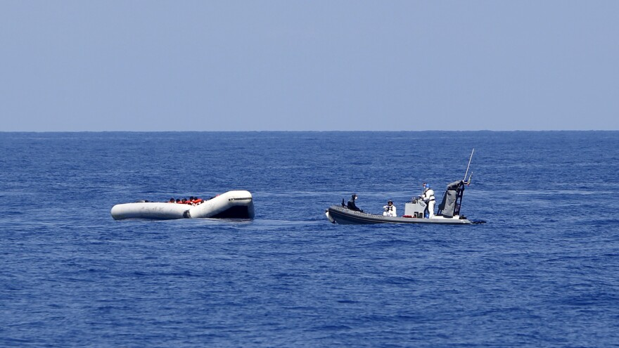 An Italian navy boat from the ship Francesco Mimbelli approaches a rubber dinghy carrying migrants during a rescue operation off the coast of Libya.