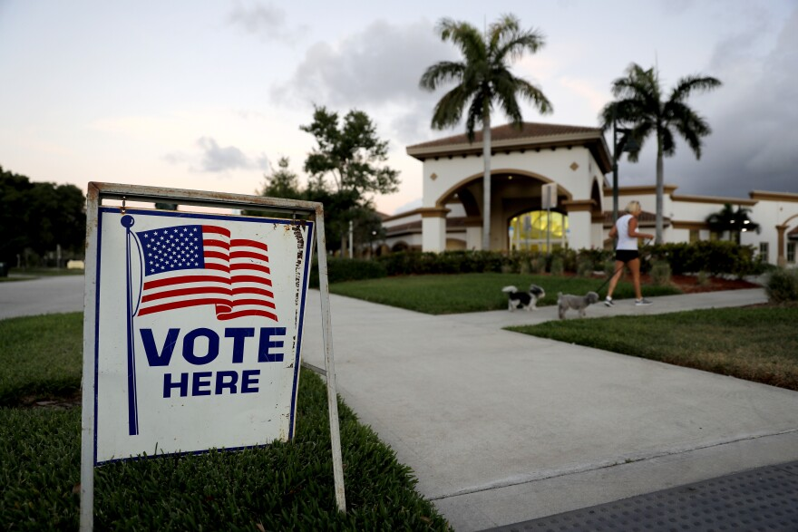 A sign is placed outside of a polling place at the Boca Raton Library during the Florida primary election, Tuesday, March 17, 2020, in Boca Raton, Fla.  As Florida officials try to contain the spread of the novel coronavirus, the state's voters will head to the polls and cast ballots in the Democratic presidential primary.