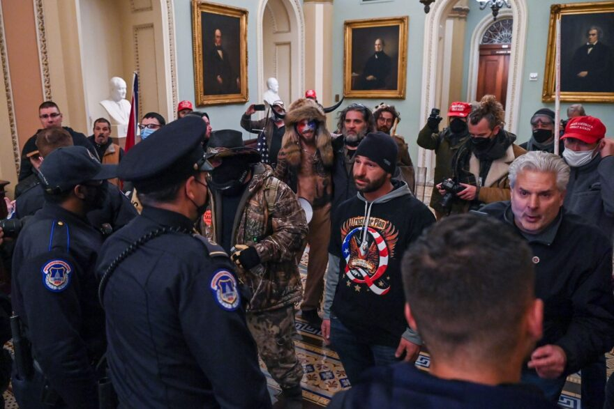 A man wearing a QAnon sweatshirt protests against US Capitol police officers as they try to stop supporters of US President Donald Trump from entering the Capitol in Washington, DC.