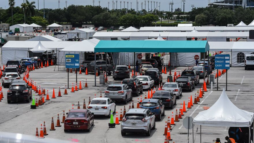 Cars line up last month at a rapid coronavirus testing site at Hard Rock Stadium in Miami Gardens, Fla. Florida's agencies have cut ties with the testing lab Quest Diagnostics over the delayed reporting of tens of thousands of test results to the state.