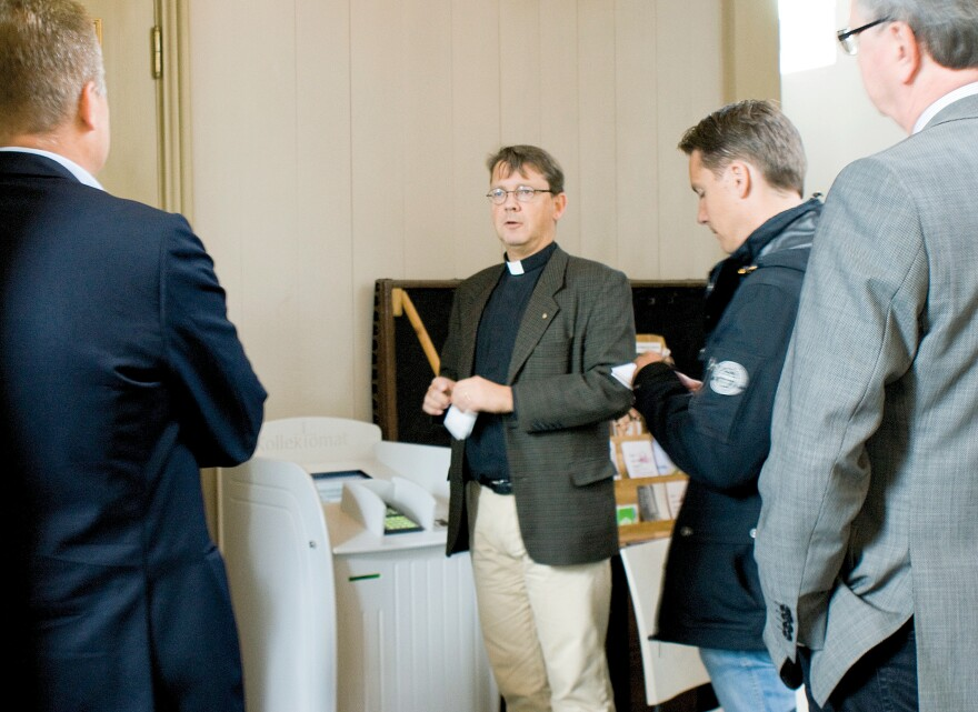 Vicar Johan Tyrberg of the Carl Gustaf Church in Karlshamn, southern Sweden, stands next to a credit card machine enabling worshippers to donate money to the church collection electronically, in 2011.