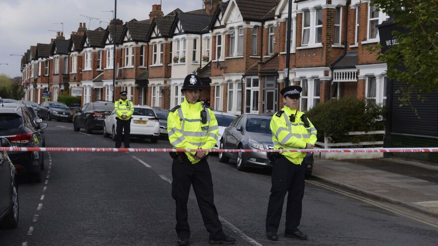 Police cordon off part of London's Harlesden Road on Friday, after counterterrorism police shot a woman and arrested several people in raids in London and southeastern England.