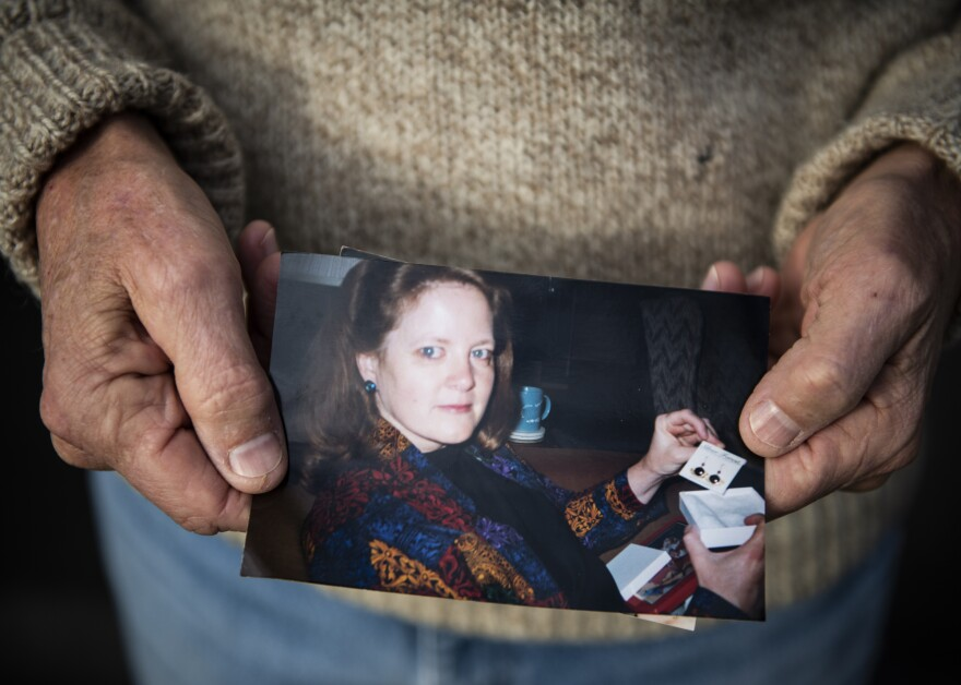 Scott Williams holds a favorite photo of his late wife, Debbie, outside his home in Lebanon, Ind. Debbie died in April of hypothyroidism. The family has yet to have a proper funeral due to the pandemic.