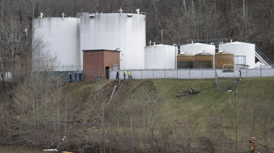Workers inspect an area near storage tanks where a chemical leaked into the Elk River at Freedom Industries storage facility in Charleston, W.Va., on Jan. 13. It is still unclear exactly how much of the chemicals leaked into the area's water supply.