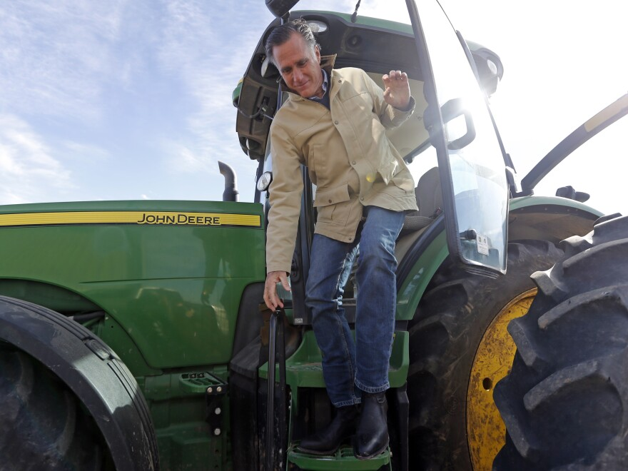 Former Republican presidential candidate Mitt Romney climbs down from a tractor during a tour of Gibson's Green Acres Dairy Friday, Feb. 16, in Ogden, Utah. Romney hopes to win the seat being vacated by retiring seven-term Utah Sen. Orrin Hatch.
