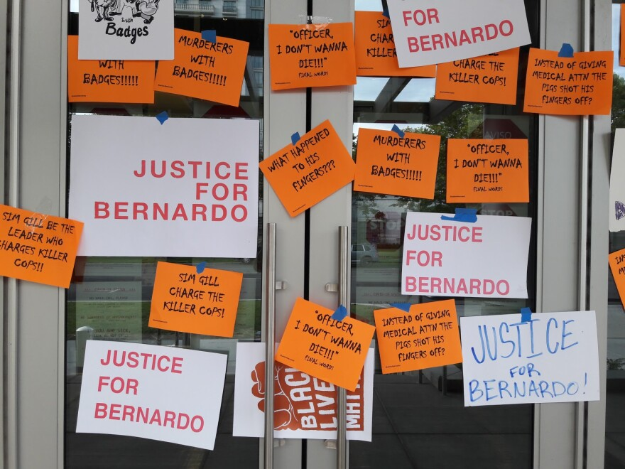 """Photo of glass doors covered in posters that say things like """"Justice for Bernardo"""" and Palacio-Carbajal's reported last words."""