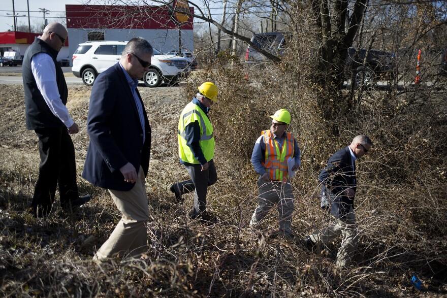 Gov. Mike Parson embarks down a hill on Feb. 14, 2019, to examine a bridge near Fenton.