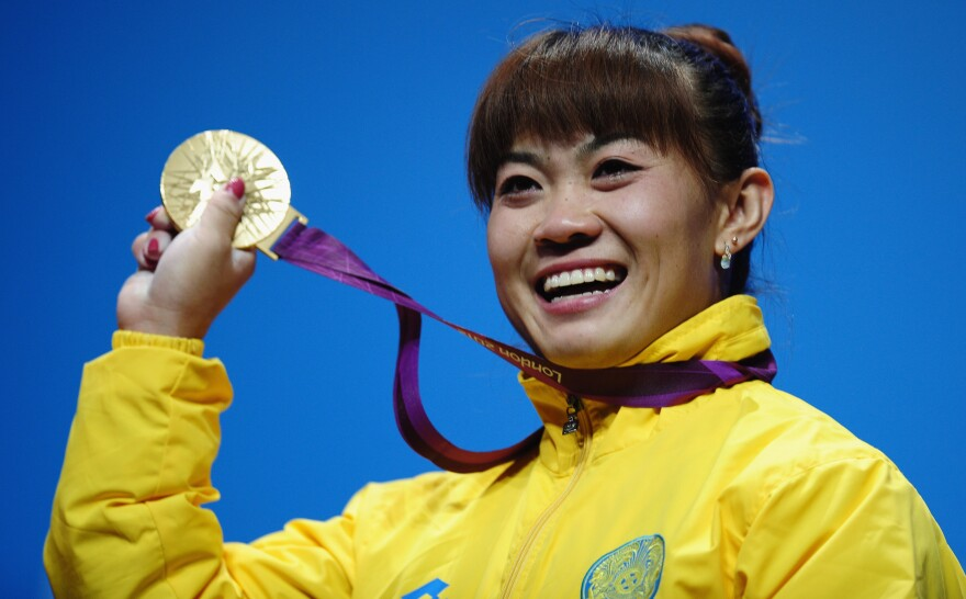 <strong>Plenty To Smile About:</strong> Weightlifter Maiya Maneza of Kazakhstan celebrates on the podium with her new 400-gram gold medal, matching the feat of her compatriot Zulfiya Chinshanlo. The Kazakh Olympians will each receive a $250,000 bonus.