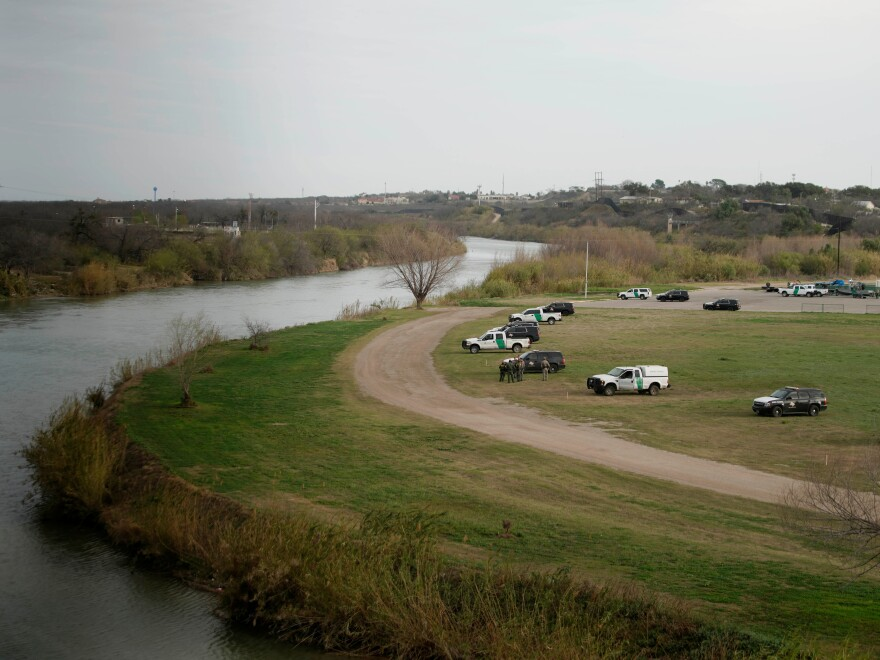 U.S. Border Patrol cars are seen from the bridge connecting Eagle Pass, Texas, with Piedras Negras, Mexico, near the banks of the Rio Grande in February.