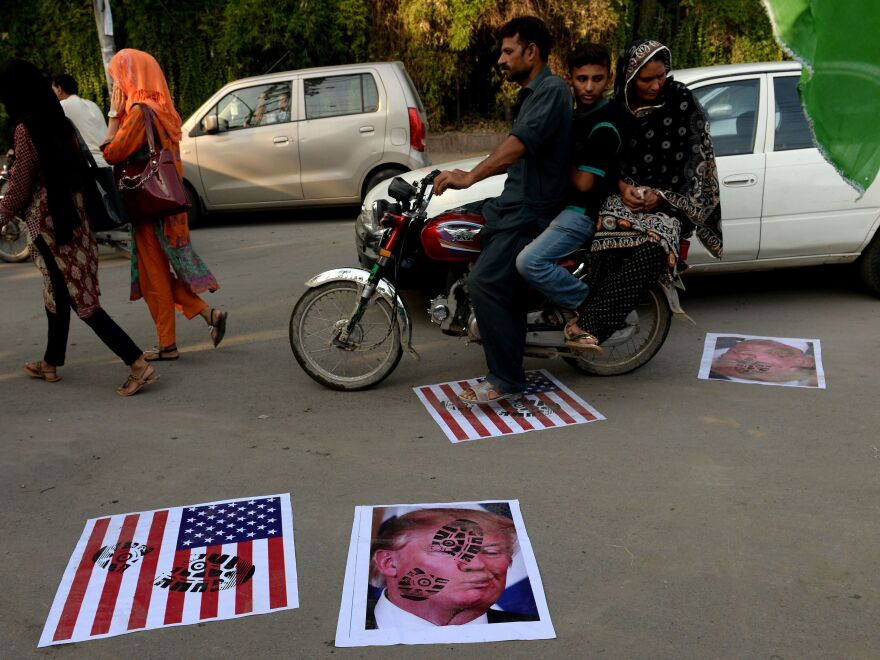 A Pakistani motorcyclist rides over images of President Trump in August 2017 after Trump accused Pakistan of harboring militants.