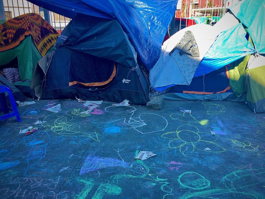 Children's artwork adds color to a tent encampment near the Paso del Norte International Bridge.