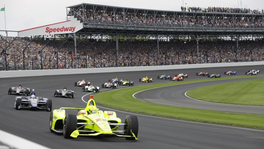 The Indianapolis 500 — usually viewed by hundreds of thousands of spectators — will be run in August in front of a crowd capped at 50% capacity, track officials say. Here, cars race in front of fans during last year's event.
