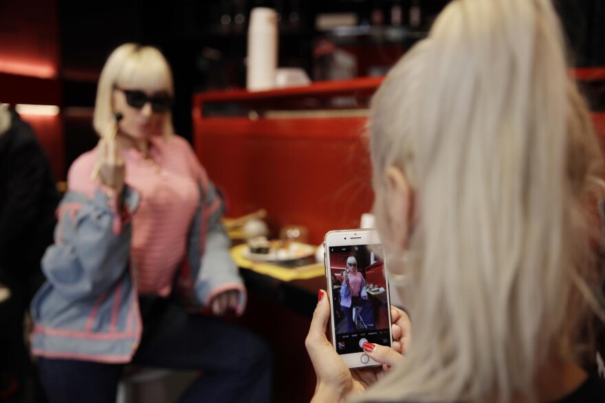 """Customer Fashion blogger Clizia Incorvaia, right, takes pictures of her friend singer Vittoria Hyde as they have lunch at the 'This is not a Sushi bar' restaurant, in Milan, Italy, Tuesday, Oct. 16, 2018. Although this is the sixth restaurant the brand """"This is not a sushi bar"""" opens in Milan, it has one key difference from its other locations: here payment can be made according to the number of Instagram followers one has, attracting big time social influencers and holders of smaller accounts alike. (AP Photo/Luca Bruno)"""