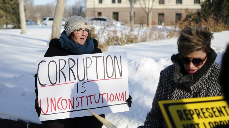 Roxanne Weber (left) rallies in support of a voter-approved government ethics overhaul in front of the South Dakota Capitol in Pierre last month. Republican Gov. Dennis Daugaard said he supports efforts to repeal and replace the initiative.