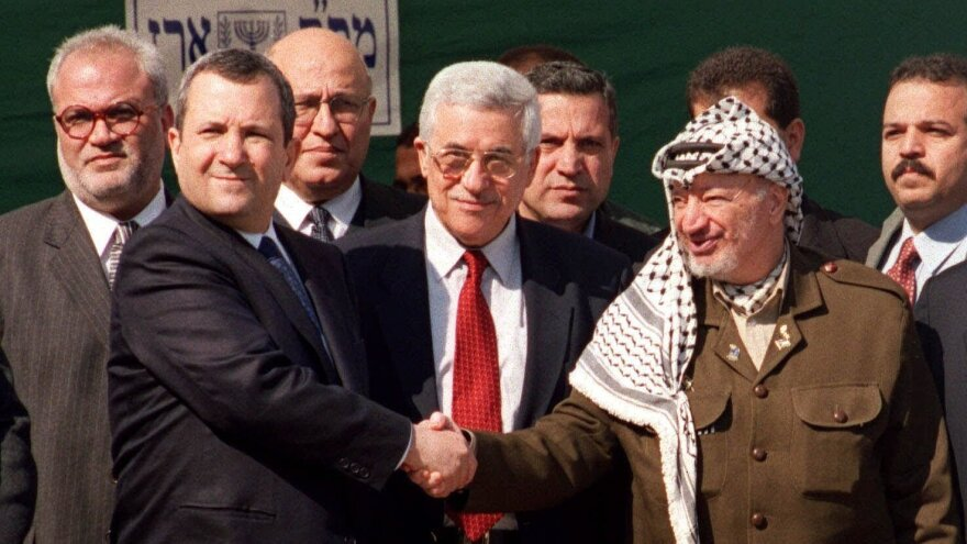 Chief Palestinian negotiator Saeb Erekat (farthest to the left), with Israeli and Palestinian officials as Israeli Prime Minister Ehud Barak (left) and PLO Chairman Yasser Arafat (right) shake hands before a summit at the Erez Crossing in the Gaza Strip in 2000.