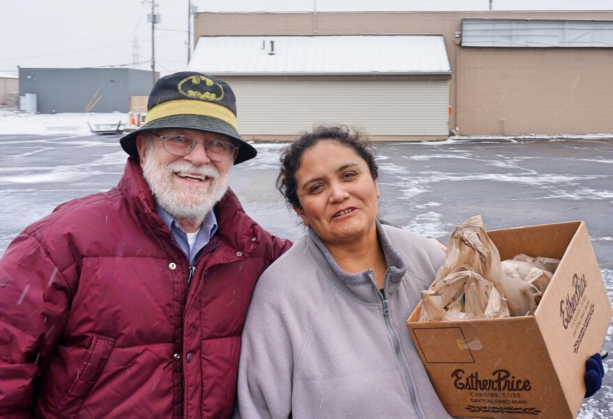Bill Evans helps Ana Moreno unload her groceries. The Old North Dayton neighborhood association says it will provide residents with free rides to a nearby grocery store every Saturday morning for the next few months while waiting for GroceryLane to reopen