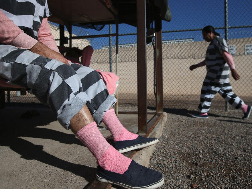 An inmate exercises while another sits on his bunk at the Maricopa County tent city jail for inmates who are in the country illegally on March 11, 2013 in Phoenix.