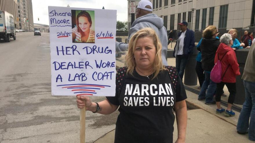 A photo outside the federal courthouse in Cleveland, of Brenda Ryan holding up a photo of her daughter, Sheena Moore, who died of an overdose.