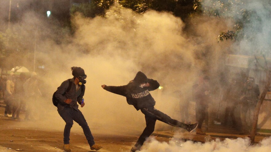 Protesters stand amid tear gas fired by police during a protest against the reelection of President Evo Morales outside the top electoral court in La Paz, on Wednesday.