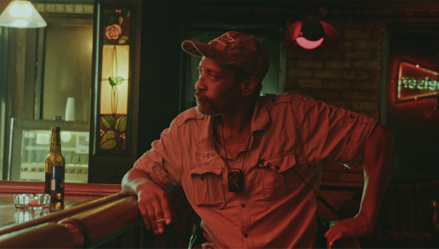 Screenshot of the film Bloody Nose, Empty Pockets. Picture is of a man sitting at a bar.
