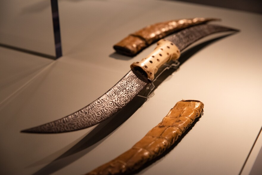 This double-bladed dagger, with the design on the blade etched with acid, is from late 19th-century Sudan and is made of iron, bone and crocodile skin.