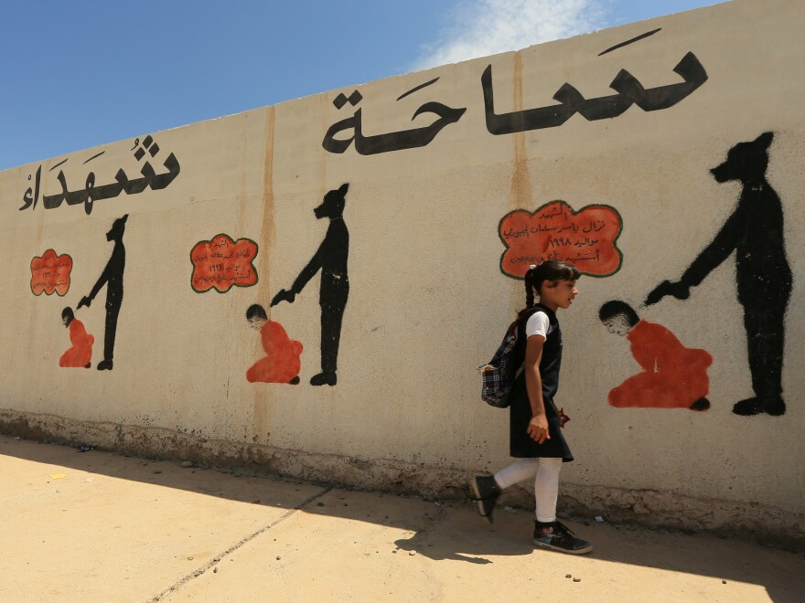 In Mosul, reminders of the Islamic State's brutal rule include a school wall covered with drawings showing how militants executed their prisoners. The U.N. says the area around the city holds mass graves where thousands of people were buried.