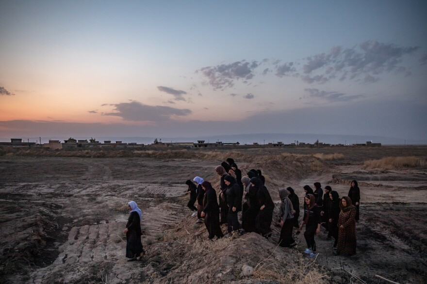 Survivors of the ISIS genocide of Yazidis walk to mass graves near the village of Kocho, northern Iraq, in August 2019, on the fifth anniversary of the massacre that killed almost all the men and older boys in the village.