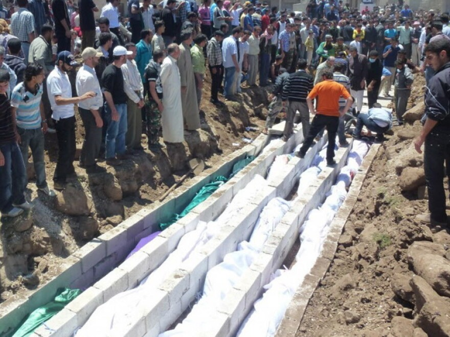 May 26, 2012: In this picture provided by the Syrian opposition's Shaam News Network, people watch the mass burial of victims in Houla.