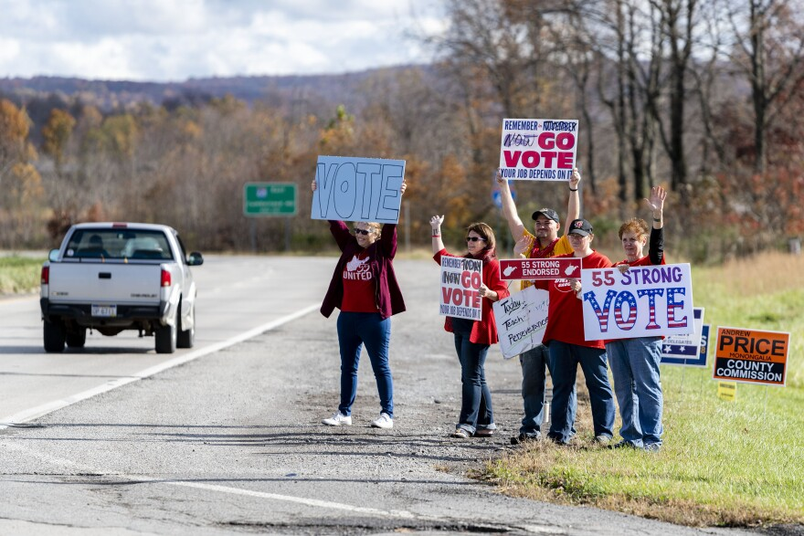 Teachers hold signs and wave at motorists on Cheat Road on Election Day, Tuesday, Nov. 6, 2018, outside Morgantown, W.Va.