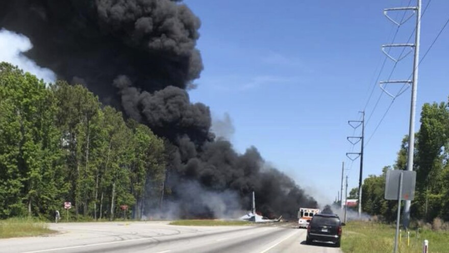 Flames and smoke rise from the wreckage of an Air National Guard C-130 after it crashed Wednesday on a roadway outside Savannah, Ga.