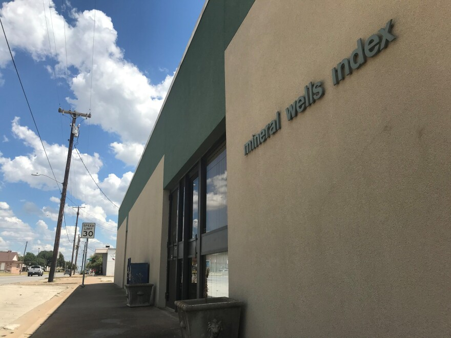 "In this photo, a squat building with darkened windows has the words ""Mineral Wells Index"" on the front. Dead plants are in the planters by the door."