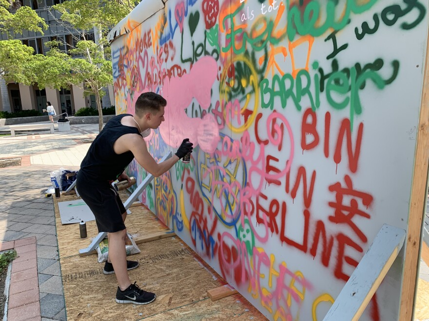 Kaelan Dean spray paints graffiti on Berlin Wall replica