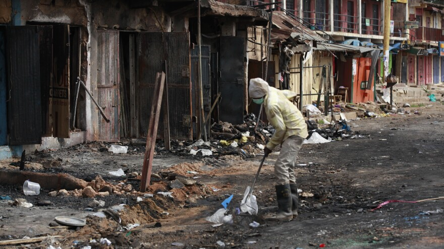 A man cleans up the site of Tuesday's car bomb explosion in Jos, Nigeria, on Thursday. The city was spared deadly reprisals, in part because a peace group intervened.