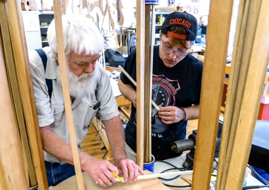 Paul Williams (left) helps Scott Beatty build his 'backpack' guitar. It has a smaller body, meant to easily fit in a pack. Beatty is in the Culture of Recovery program which teaches instrument making to people recovering from addiction.