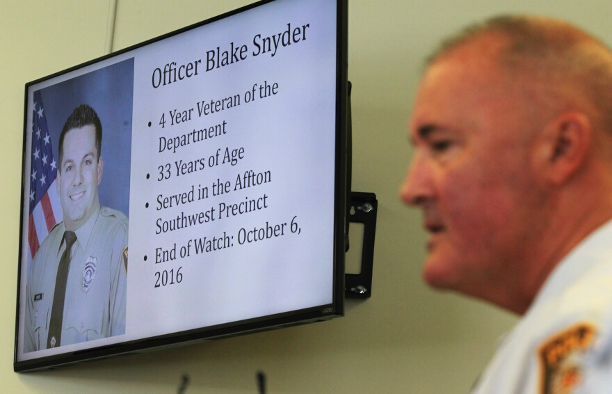 St. Louis County Police Chief Jon Belmar gives details of a shooting death of Officer Blake Snyder as a photo of the officer is shown during a press conference in Clayton. 10-06-16