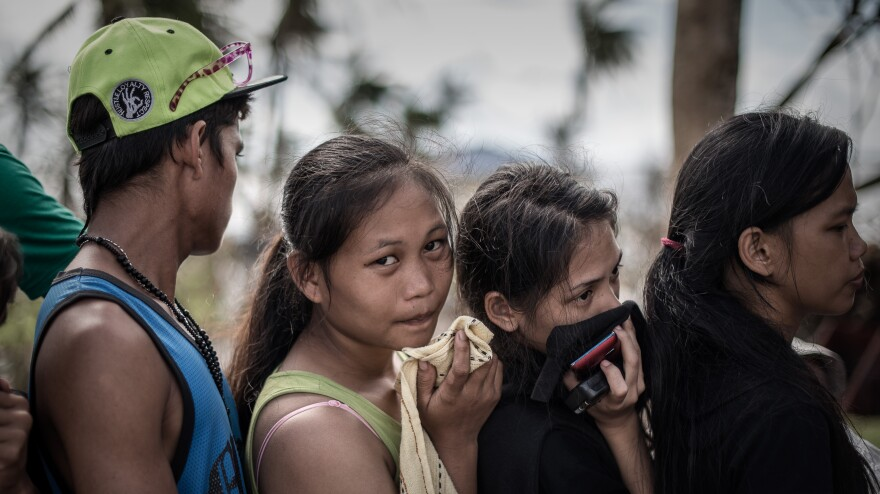In Tacloban, the Philippines, on Thursday, some survivors waiting in a line to charge cellphones covered their faces because of the lingering smell of dead bodies.