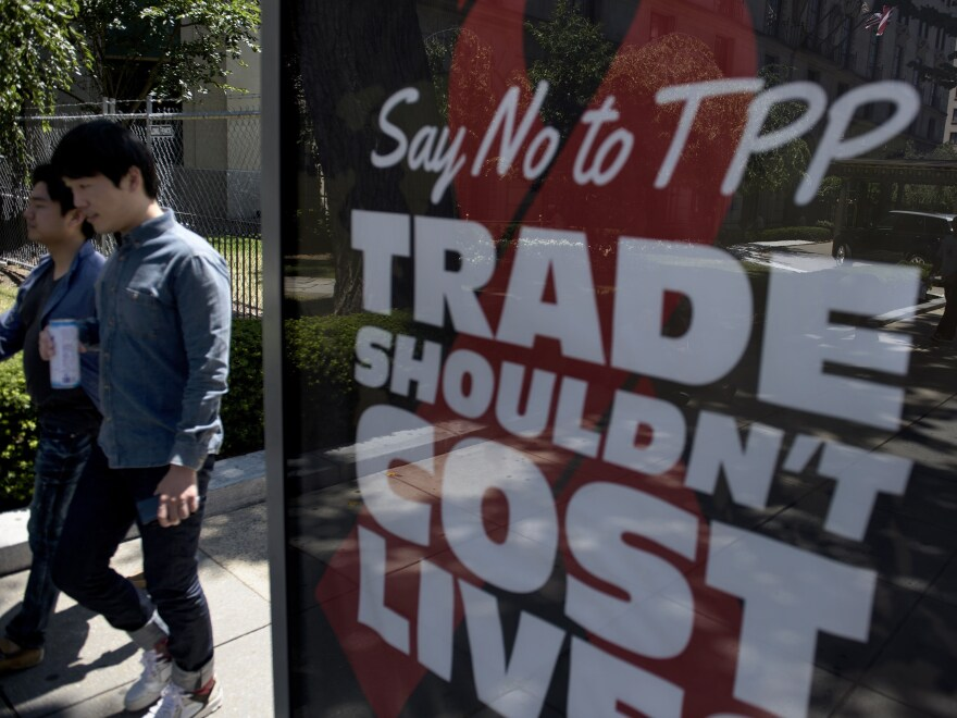 Passersby in Washington, D.C., walk near an ad protesting the Trans-Pacific Partnership in July.